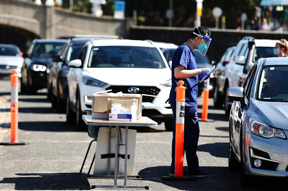A healthcare worker wearing personal protective equipment (PPE) speaks to a driver at a drive-in Covid-19 testing site set up in the Bondi suburb of Sydney.