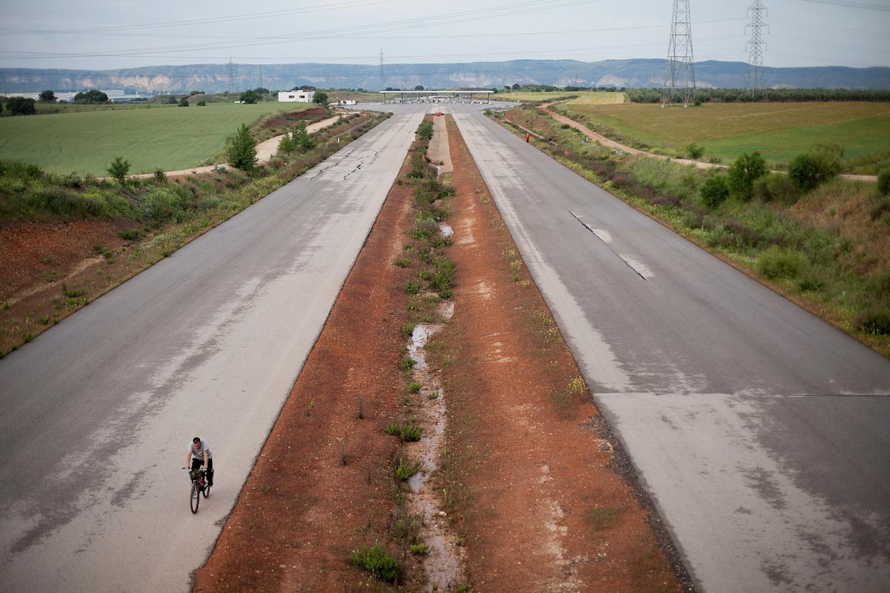 MADRID, SPAIN - MAY 15:  A man rides his bicycle a long the MP-203 highway project near Mejorada del Campo on May 15, 2013 in Madrid, Spain. The MP-203 highway, which was built to decongest the Barcelona highway (A-2), has remained unfinished for 6 years after an initial investment 70 millions Euro between 2005 and 2007. Despite the completion of around 70 percent of the 12.5 kilometer project it was stopped after issues arose with the Madrid - Barcelona high speed railway and the connection to the R-3 highway.  (Photo by Pablo Blazquez Dominguez/Getty Images)