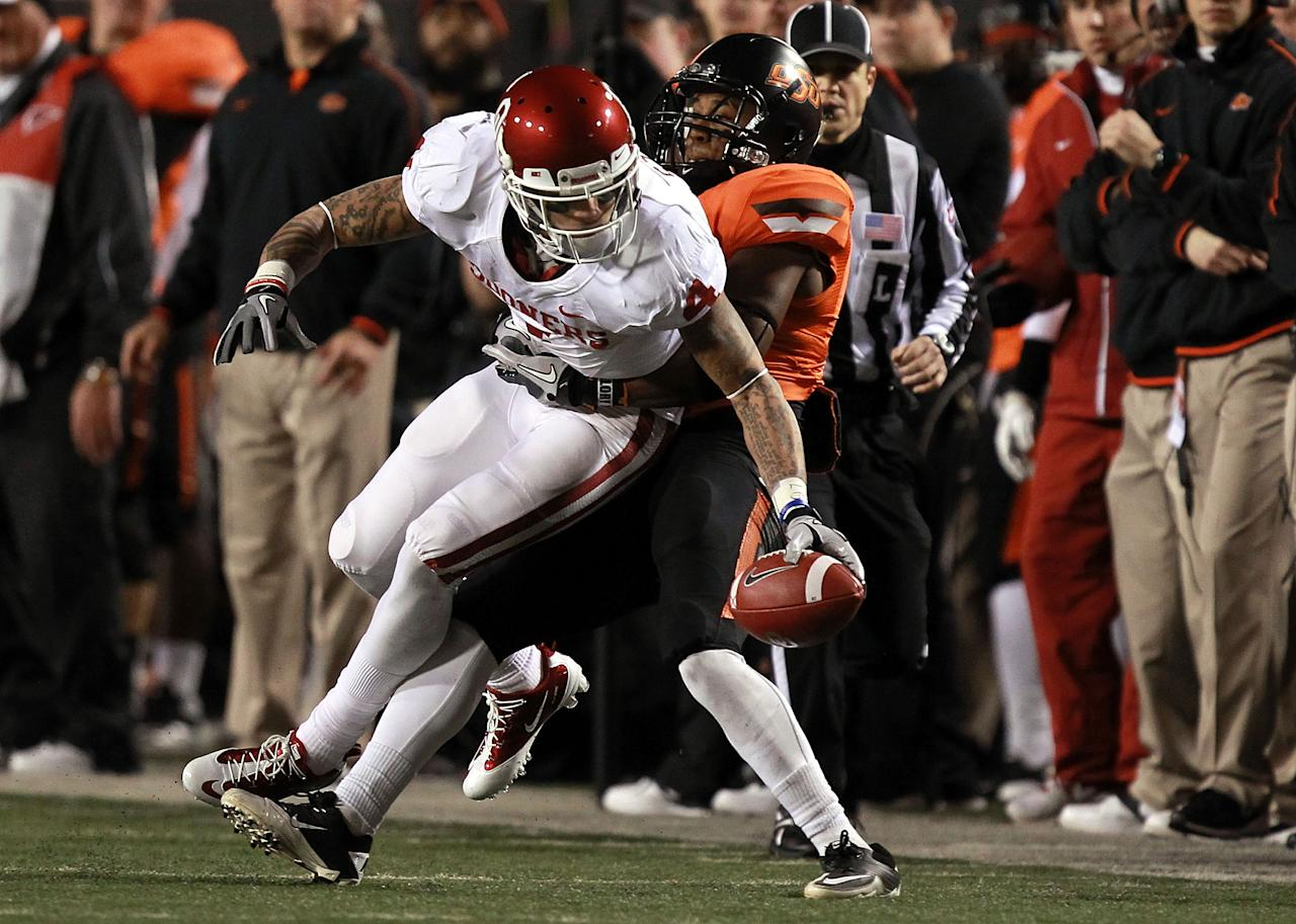 STILLWATER, OK - DECEMBER 03:  Kenny Stills #4 of the Oklahoma Sooners is tackled by Brodrick Brown #19 of the Oklahoma State Cowboys at Boone Pickens Stadium on December 3, 2011 in Stillwater, Oklahoma.  (Photo by Ronald Martinez/Getty Images)