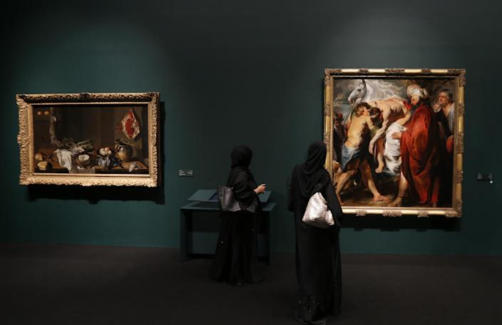 Emirati visitors walk past paintings that are part of 130 artworks featured at the first large-scale presentation of the permanent collection of Abu Dhabi's planned Louvre Museum on April 21, 2013 (AFP Photo/Karim Sahib)