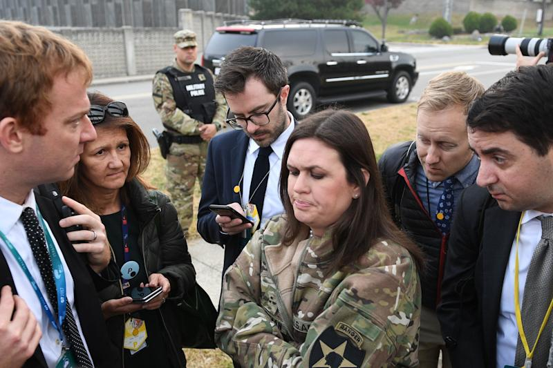 White House press secretary Sarah Huckabee Sanders (center) speaks to reporters after the helicopters returned from the aborted DMZ visit. (JIM WATSON/AFP/Getty Images)