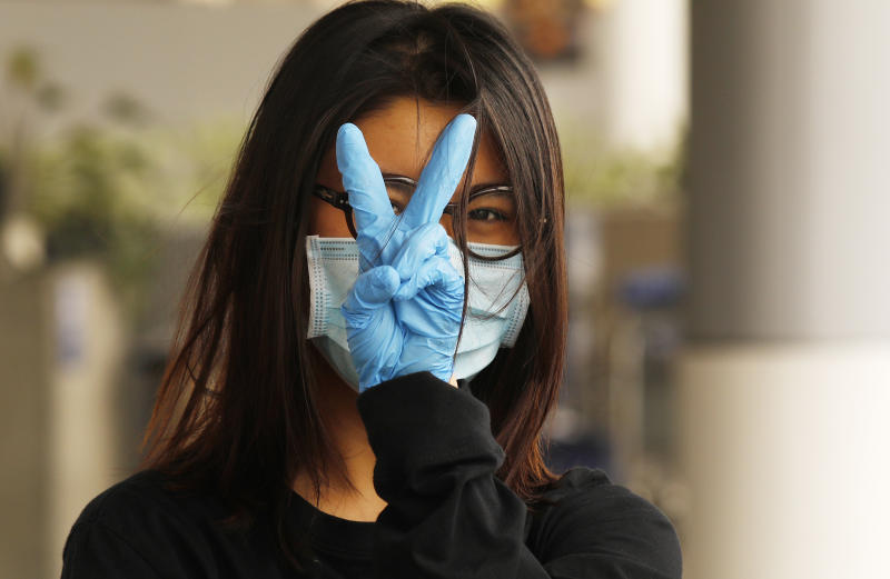 LOS ANGELES, CA - MAY 11: Yiran Zou, a student at the California College of Art in San Francisco prepares to fly home to China at Tom Bradley International Terminal, Los Angeles International Airport (LAX) which is now requiring travelers to wear face covering to help keep fellow passengers and crew safe by limiting the spread of the coronavirus Covid-19. The new requirements for wearing face masks in Los Angels began Monday at LAX and on local public transit. LAX on Monday, May 11, 2020 in Los Angeles, CA. (Al Seib / Los Angeles Times via Getty Images)