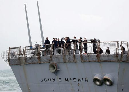 FILE PHOTO: Personnel work on the U.S. Navy guided-missile destroyer USS John S. McCain after a collision, in Singapore waters August 21, 2017. REUTERS/Ahmad Masood/File Photo