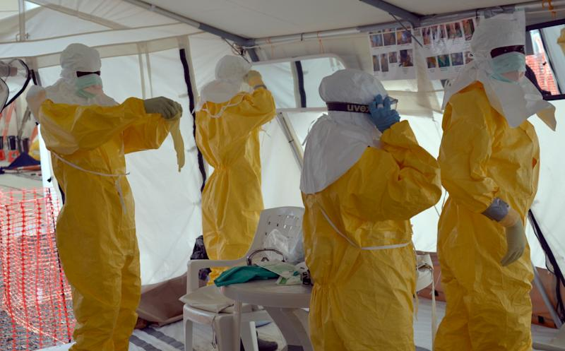 Liberian health workers don full protection outfits at a Medecins Sans Frontieres Ebola treatment center in Monrovia, on October 18, 2014 (AFP Photo/Zoom Dosso)