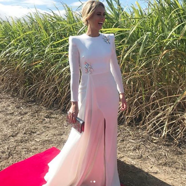 <p>The television presenter stuns in this whimsical white dress designed by Alex Perry which she paired with a Christian Dior clutch. Source: Instagram/Channel9Style </p>