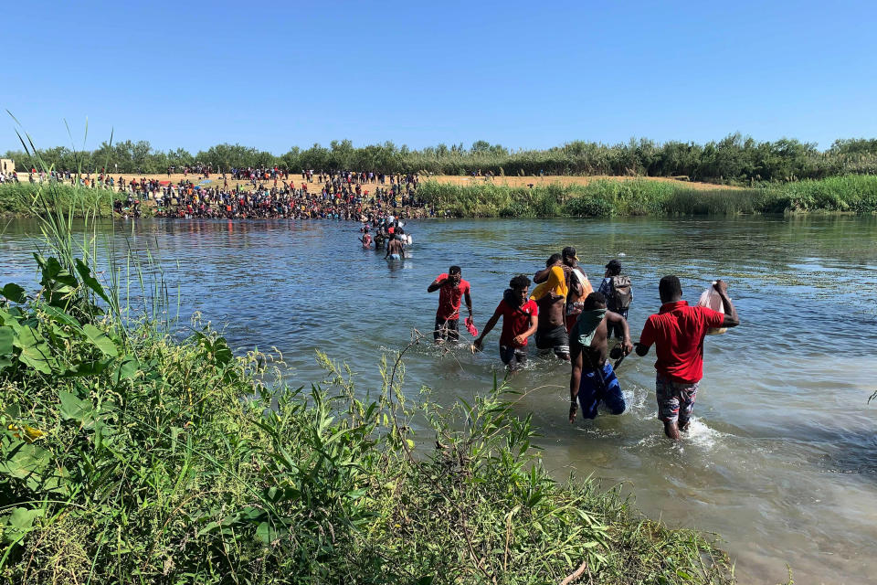 Migrants find an alternate place to cross from Mexico to the United States after access to a dam was closed, Sunday, Sept. 19, 2021, in Ciudad Acuña, Mexico. U.S. officials said that within the next few days, they plan to ramp up expulsion flights for some of the thousands of Haitian migrants who have gathered in the Texas city from across the border in Mexico. (AP Photo/Sarah Blake Morgan)