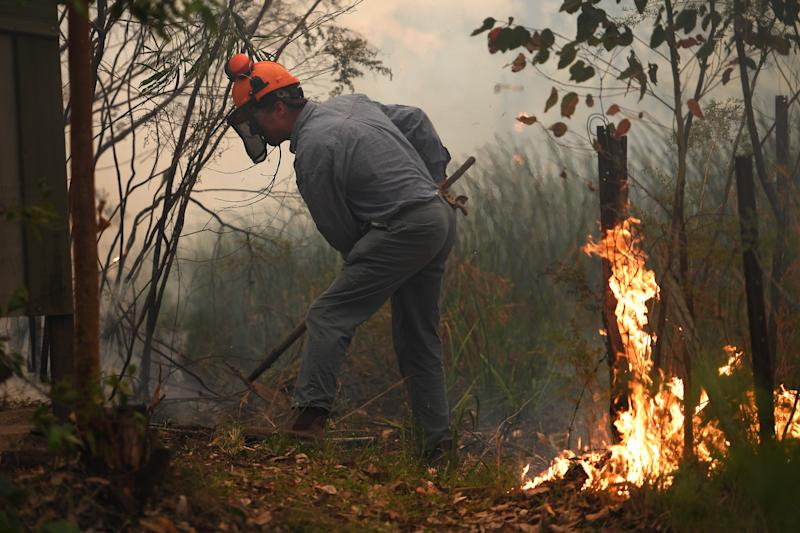 Homeowner Rod Meggs puts out spot fires as NSW Rural Fire Service and Fire and Rescue NSW crews work to protect his property on Kyola Road in Kulnura as the Wrights Creek fire approaches Mangrove Mountain north of Sydney.
