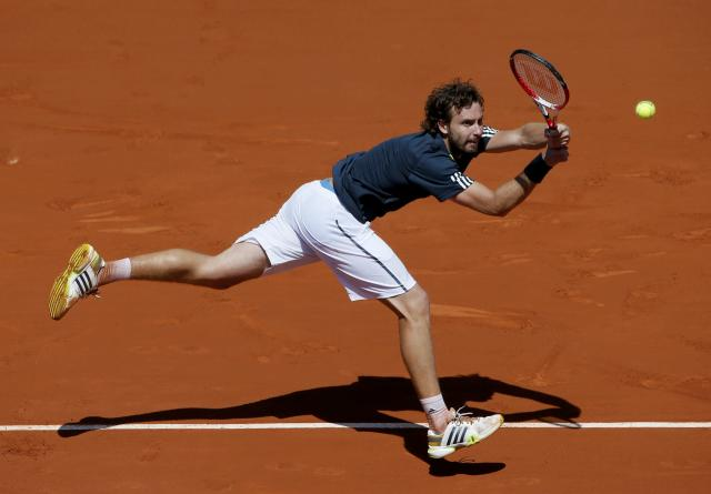 Ernests Gulbis of Latvia returns the ball to Novak Djokovic of Serbia during their men's semi-final match at the French Open tennis tournament at the Roland Garros stadium in Paris June 6, 2014. REUTERS/Gonzalo Fuentes (FRANCE - Tags: SPORT TENNIS)