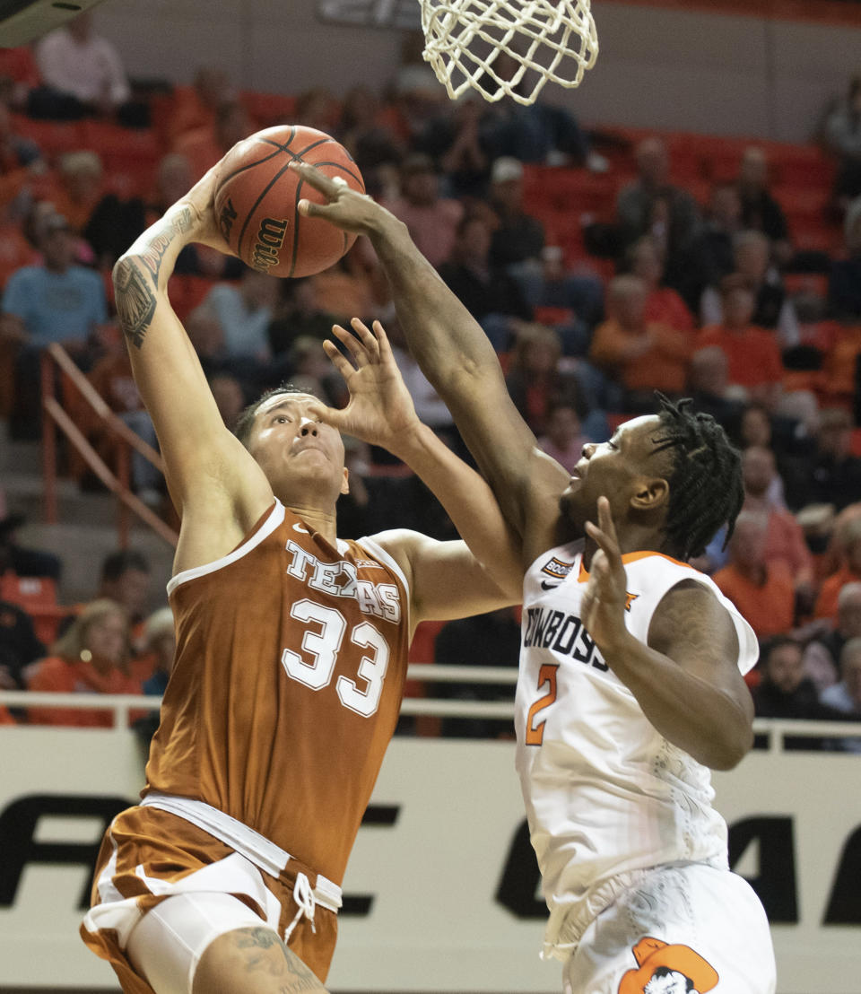 Oklahoma State guard Chris Harris Jr. (2) attempts to block a dunk by Texas forward Kamaka Hepa (33) during the second half an NCAA college basketball game in Stillwater, Okla., Wednesday, Jan. 15, 2020. (AP Photo/Brody Schmidt)