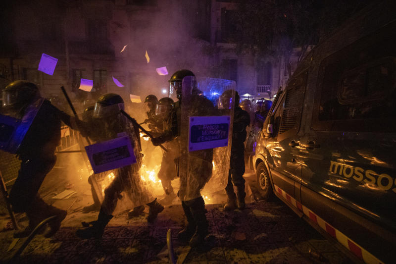 Policemen in riot gear move past a burning barricade during clashes with protestors in Barcelona, Spain, Tuesday, Oct. 15, 2019. (Photo: Emilio Morenatti/AP)