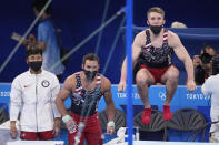Gymnasts from the United States, from left, Yul Moldauer, Samuel Mikulak, and Shane Wiskus watch teammate Brody Malone performing on the horizontal bar during the artistic men's team final at the 2020 Summer Olympics, Monday, July 26, 2021, in Tokyo. (AP Photo/Ashley Landis)