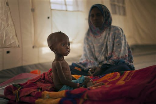 Mother Fatime Abd Rahmane, 22, looks across as her daughter Kaltouma Abdoulaye, 23 months old, sits up on her mattress where she is recovering from severe malnutrition in the intensive care tent of a clinic in Mondo, a desert village in the Sahel belt of Chad, Thursday, April 19, 2012. UNICEF estimates that 127,000 children under 5 in Chad's Sahel belt will require lifesaving treatment for severe acute malnutrition this year, with an estimated 1 million expected throughout the wider Sahel region of West and Central Africa in the countries of Niger, Nigeria, Mali, Chad, Burkina Faso, Cameroon, Senegal and Mauritania. The organization says the current food and nutrition crisis stems from scarce rainfalls in 2011, which caused poor harvests and livestock production, though the situation in Chad has also been exacerbated by an influx of Chadians returning from Libya as a result of the conflict there. (AP Photo/Ben Curtis)