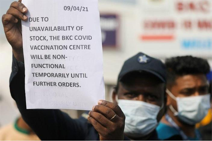 A security guard held a notice to inform people about the shortage of coronavirus vaccines (COVID-19) at a vaccination center in Mumbai, India, April 9, 2021.