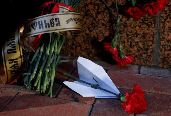 Flowers and a paper plane are placed outside the Iranian Embassy to commemorate the victims of the Ukraine International Airlines flight PS752 plane crash
