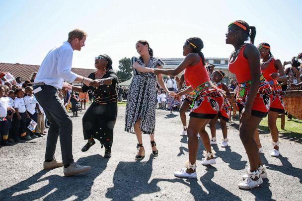 PHOTO: Prince Harry, Duke of Sussex, and Meghan, Duchess of Sussex, dance as they arrive for a visit to 'Justice desk', an NGO in the township of Nyanga in Cape Town, as they begin their tour of the region, Sept. 23, 2019. (Betram Malgas/AFP/Getty Images)
