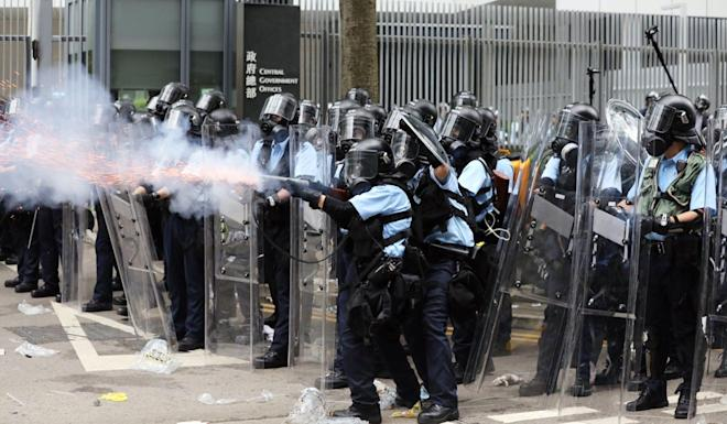 Police fire tear gas to keep protesters away from government offices. Photo: Sam Tsang