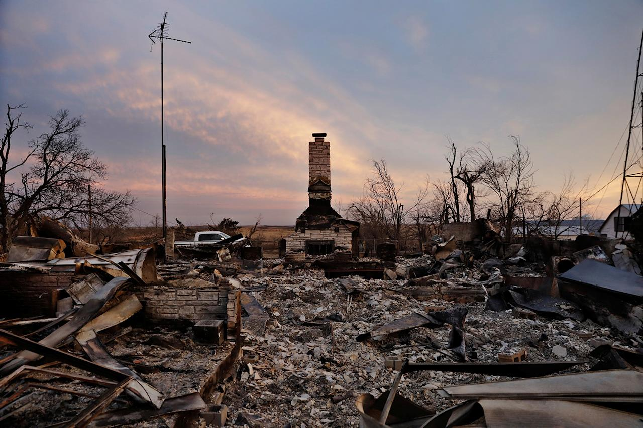 <p>A chimney is all that stands in the footprint of a home destroyed by wildfires near Laverne, Okla., March 12, 2017. (Photo: Lucas Jackson/Reuters) </p>