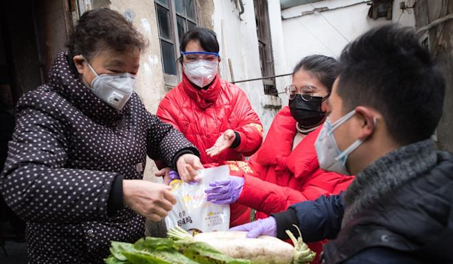 Community workers deliver food to an elderly woman in Wuhan. Tighter measures are making it harder to deliver the essentials. Photo: Xinhua