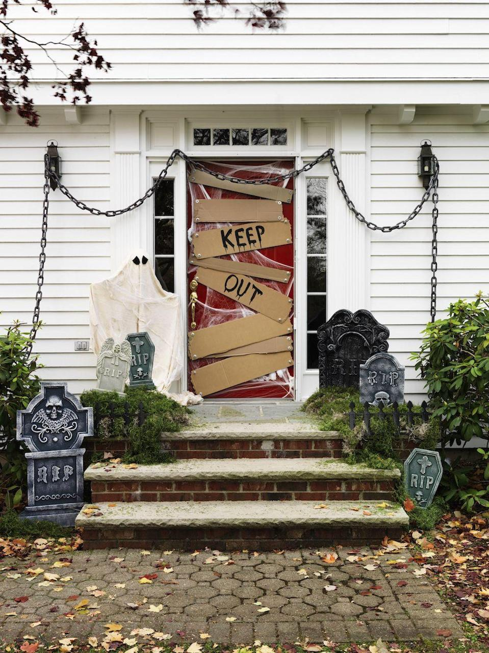 """<p>Turn your home's entrance into a graveyard—the perfect project for dedicated Halloween enthusiasts. Add a """"Keep Out"""" sign on cardboard slats, place cobwebs all over your door, hang a ghost, position a few gravestones on your steps, and you're ready to celebrate. </p><p><a class=""""link rapid-noclick-resp"""" href=""""https://www.amazon.com/YazyCraft-Webbing-Halloween-Decorations-Spiderweb/dp/B00F9RWP98?tag=syn-yahoo-20&ascsubtag=%5Bartid%7C10055.g.32948621%5Bsrc%7Cyahoo-us"""" rel=""""nofollow noopener"""" target=""""_blank"""" data-ylk=""""slk:SHOP COBWEBS"""">SHOP COBWEBS</a><br><br><em><a href=""""https://www.countryliving.com/diy-crafts/g22350299/halloween-door-decorations/?slide=17"""" rel=""""nofollow noopener"""" target=""""_blank"""" data-ylk=""""slk:See the full tutorial here >>"""" class=""""link rapid-noclick-resp"""">See the full tutorial here >></a></em> </p>"""