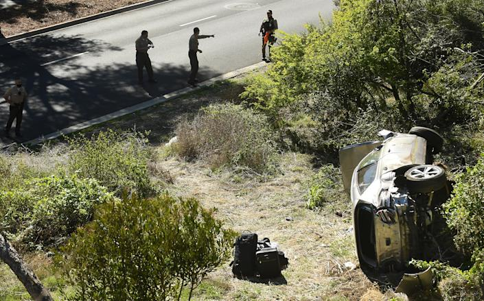 RANCHO PALOS VERDES, CALIFORNIA FEBRUARY 23, 2021-L.A. County Sheriff's officers investigate an accident involving famous golfer Tiger Woods along Hawthorne Blvd. in Ranch Paos Verdes Tuesday. (Wally Skalij/Los Angeles Times via Getty Images)