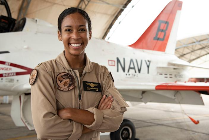Lt. j.g. Madeline G. Swegle, the U.S. Navy's first Black female tactical jet aviator, stands in front of a T-45C Goshawk jet trainer aircraft on the Training Air Wing 2 flight line at Naval Air Station Kingsville, Texas, July 17, 2020