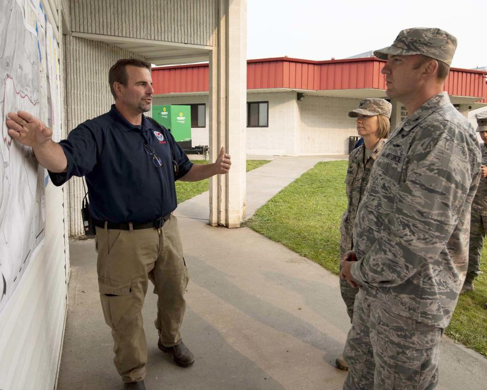 Andrew Stenbeck points to a map with members of the National Guard looking on.