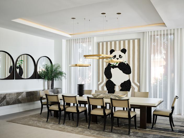 """<div class=""""caption""""> The dining room's focal point is a whimsical panda painting by Robert Pruitt. Wecselman designed the sideboard and mirrors for the space, and the table and chairs are by <a href=""""https://www.liaigre.com/en/"""" rel=""""nofollow noopener"""" target=""""_blank"""" data-ylk=""""slk:Liaigre"""" class=""""link rapid-noclick-resp"""">Liaigre</a>. Pendant lights by <a href=""""https://www.henge07.com/"""" rel=""""nofollow noopener"""" target=""""_blank"""" data-ylk=""""slk:Henge"""" class=""""link rapid-noclick-resp"""">Henge</a> hang overhead. </div>"""
