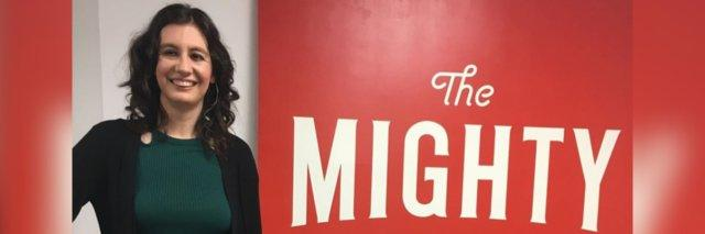 Kelly Douglas posing with The Mighty sign at the Southern California headquarters.