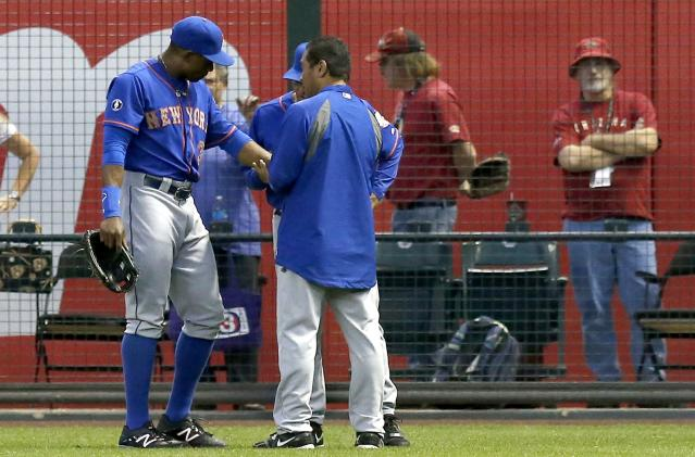 New York Mets' Curtis Granderson (3) is looked at by Mets training staff after Granderson tried to make a play on a ball hit by Arizona Diamondbacks' Miguel Montero in the first inning of a baseball game on Monday, April 14, 2014, in Phoenix. Granderson left the game early, but the Mets defeated the Diamondbacks 7-3. (AP Photo/Ross D. Franklin)