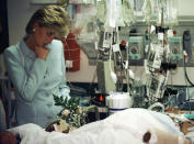 """FILE - In this June 5, 1996 file photo, Princess Diana pauses at the bed of a seriously injured man as she visits Cook County Hospital in Chicago. For someone who began her life in the spotlight as """"Shy Di,"""" Princess Diana became an unlikely, revolutionary during her years in the House of Windsor. She helped modernize the monarchy by making it more personal, changing the way the royal family related to people. By interacting more intimately with the public -- kneeling to the level of children, sitting on edge of a patient's hospital bed, writing personal notes to her fans -- she set an example that has been followed by other royals as the monarchy worked to become more human and remain relevant in the 21st century. (Beth A. Keiser,Pool Photo via AP, File)"""