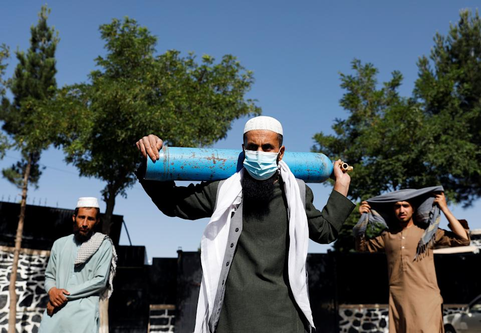 A man waits outside a factory to get his oxygen cylinder refilled as he holds it on his shoulder, amidst the spread of the coronavirus disease (COVID-19) in Kabul, Afghanistan June 15, 2021. REUTERS/Stringer
