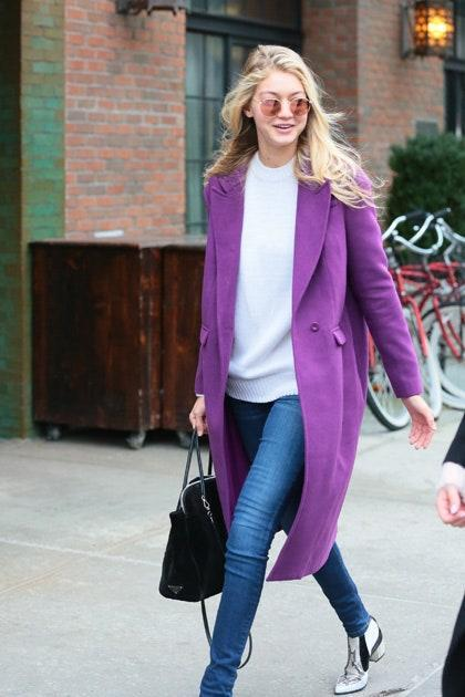 Ah, mirrored sunnies. By now, the reflective eyewear is a staple in Gigi's wardrobe, and this pair literally has her seeing through rose-colored glasses. Her bright purple coat is another bold choice, only to be outdone by her rock n' roll style white snakeskin boots. A+.