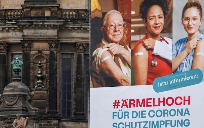 A giant billboard calling for people to get vaccinated which reads 'Roll up your sleeves for the corona vaccine', hangs on the facade of the Cathedral in Berlin's Mitte district - AFP