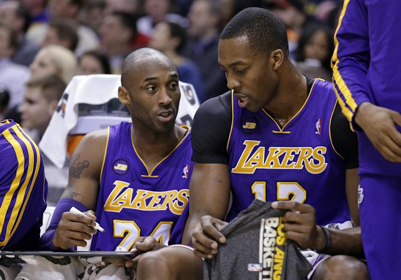 Los Angeles Lakers guard Kobe Bryant, left, draws a play for center Dwight Howard as they sit on the bench in the first half of an NBA basketball game against the Indiana Pacers in Indianapolis, Friday, March 15, 2013.  (AP Photo/Michael Conroy)