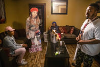 Brione Rogers sits on the couch next to a cutout of her cousin Todriana Peters and Peters' mother Katrina Lambert and father Todd Peters in New Orleans, Thursday, July 8, 2021. Twelve-year-old Todriana Peters was shot and killed outside a graduation party on Memorial Day Weekend in the Lower 9th Ward neighborhood. Homicide rates in many American cities have continued to rise although not as precipitously as the double-digit jumps seen in 2020 and still below the violence of the mid-90s. (AP Photo/Sophia Germer)