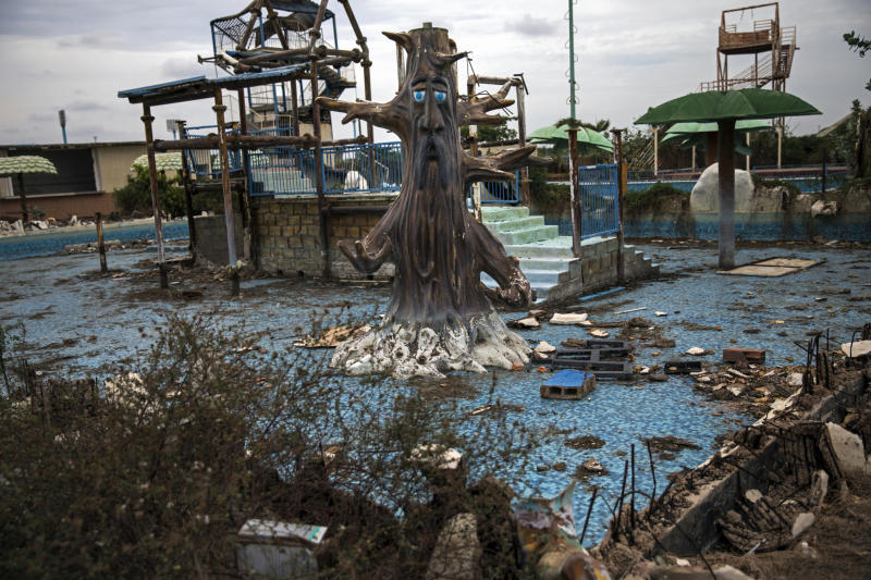 "A theme-pool lays in ruins at an abandoned amusement park coined ""Diversions Grano de Oro"" in Maracaibo, Venezuela, May 23, 2019. Many structures in Maracaibo are littered with debris and reminiscent of wartime or the aftermath of a natural disaster. (AP Photo/Rodrigo Abd)"