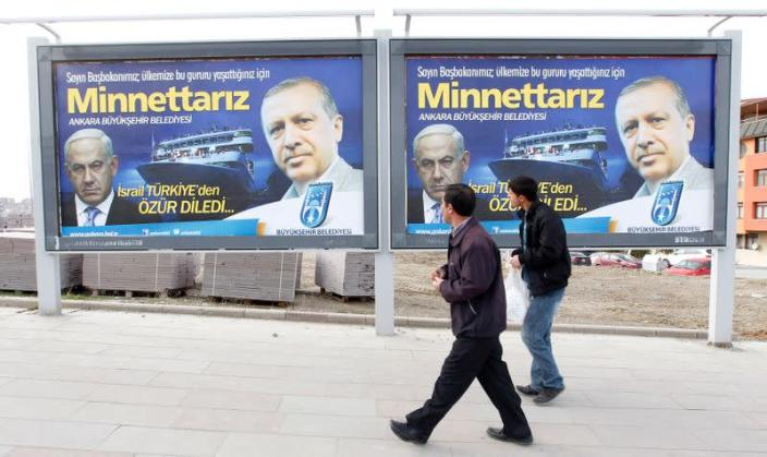 Pedestrians look at billboards with the pictures of Turkey's Prime Minister Erdogan and his Israeli counterpart Netanyahu in Ankara