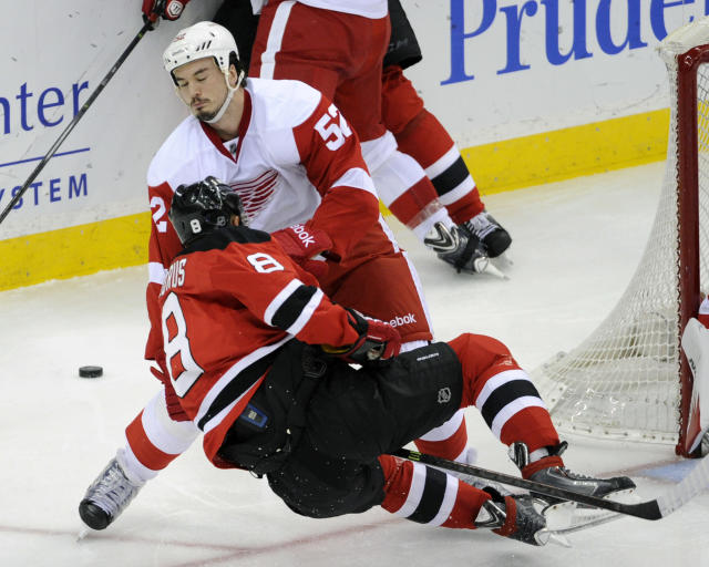 Detroit Red Wings' Jonathan Ericsson (52), of Sweden, checks New Jersey Devils' Dainius Zubrus, of Lithuania, during the second period of an NHL hockey game Tuesday, March 4, 2014, in Newark, N.J. (AP Photo/Bill Kostroun)