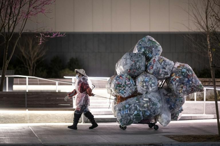 A woman wearing a face mask and a plastic bag pulls a cart loaded with bags of recyclables through the streets of Lower Manhattan