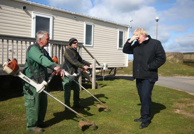 Prime Minister Boris Johnson speaks with staff during a visit to Haven Perran Sands Holiday Park in Perranporth, Cornwall