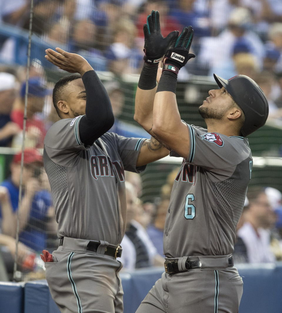 Arizona Diamondbacks' David Peralta greeted at dugout by teammate Ketel Marte after he hit a home run against the Toronto Blue Jays in the sixth inning of a baseball game Friday, June 7, 2019, in Toronto. (Fred Thornhill/The Canadian Press via AP)