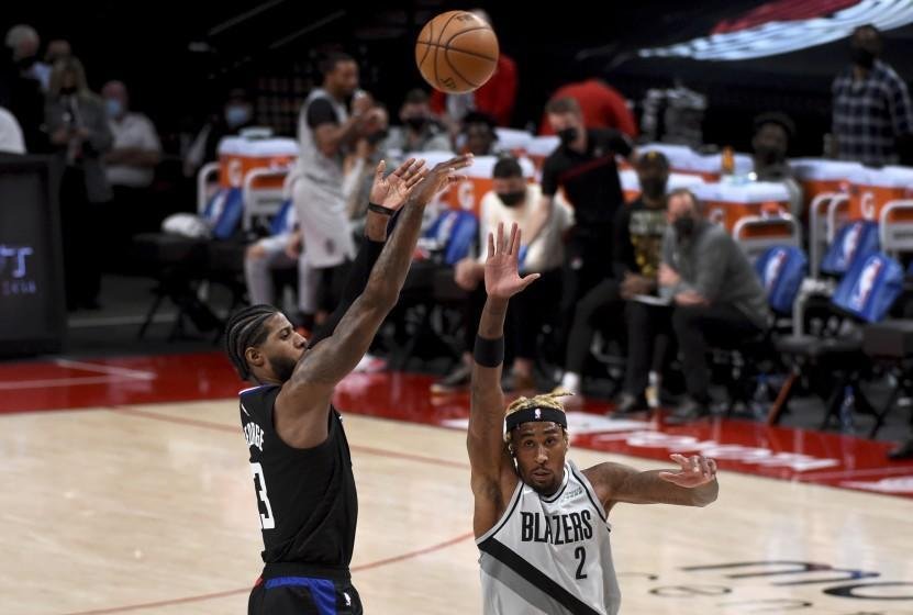 Los Angeles Clippers guard Paul George, left, hits a shot over Portland Trail Blazers forward Rondae Hollis-Jefferson, right, during the first half of an NBA basketball game in Portland, Ore., Tuesday, April 20, 2021. (AP Photo/Steve Dykes)