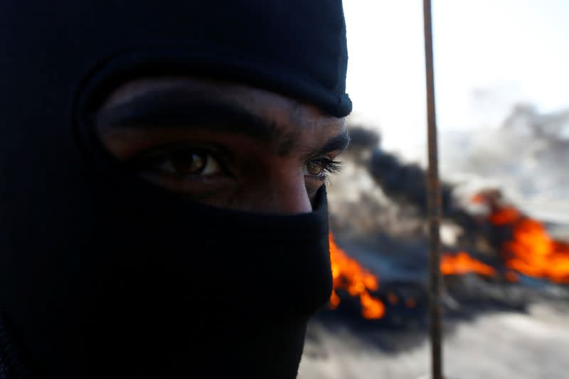 An Iraqi demonstrator covers his face near burning tires blocking a road during ongoing anti-government protests in Najaf