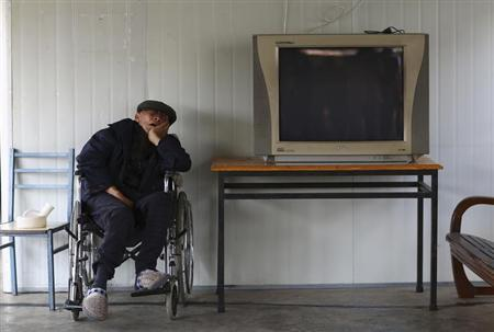 A man sleeps on a wheelchair next to a television set at a nursing home on the Double Ninth Festival, or Chongyang Festival, in Kunming, Yunnan province