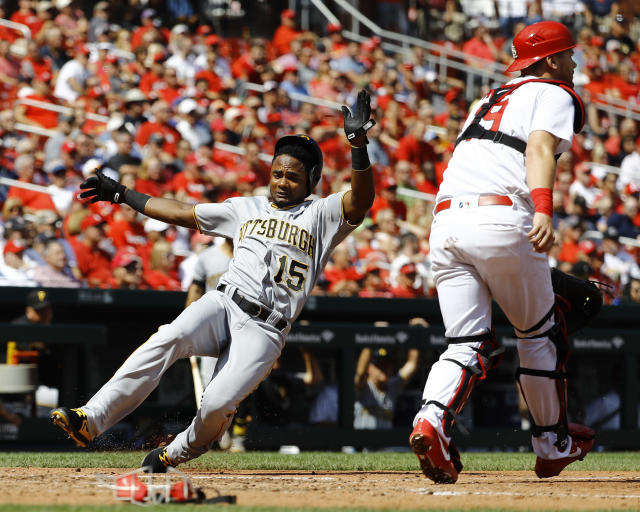 Pittsburgh Pirates' Pablo Reyes, left, slides in safely as St. Louis Cardinals catcher Carson Kelly waits for the throw during the sixth inning of a baseball game Wednesday, Sept. 12, 2018, in St. Louis. (AP Photo/Billy Hurst)