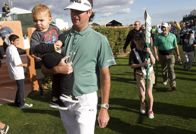 Bubba Watson holds his 1-year-old son, Caleb Watson, after finishing the third round of the Phoenix Open golf tournament, Saturday, Feb. 1, 2014, in Scottsdale, Ariz. (AP Photo/The Arizona Republic, David Wallace) MESA OUT MARICOPA COUNTY OUT MAGS OUT NO SALES