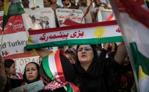 Iraqi Kurds wave flags and chant slogans during a protest outside the US consulate - Credit: Chris McGrath/Getty Images