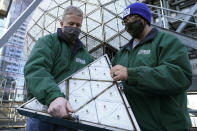 Workers from Landmark Signs carefully carry a panel of Waterford crystal triangles to place on the Times Square New Year's Eve ball, behind them, Sunday, Dec. 27, 2020, in New York, in preparation for the New Year's Eve ball drop. (AP Photo/Kathy Willens)