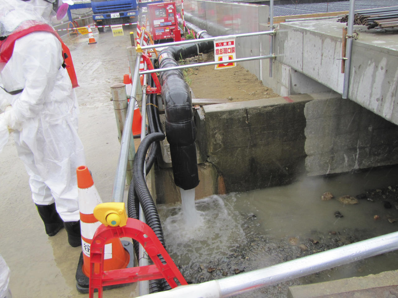 In this photo provided by Tokyo Electric Power Co. (TEPCO), underground water is being released into the ocean through a piping at Fukushima Dai-ichi nuclear plant in Okuma, Fukushima prefecture, northern Japan Wednesday, May 21, 2014. Japan's crippled nuclear power plant has begun releasing groundwater from the least contaminated areas of the facility into the ocean so it does not run into contaminated areas and create more toxic water amid storage space limitations. (AP Photo/Tokyo Electric Power Co. )