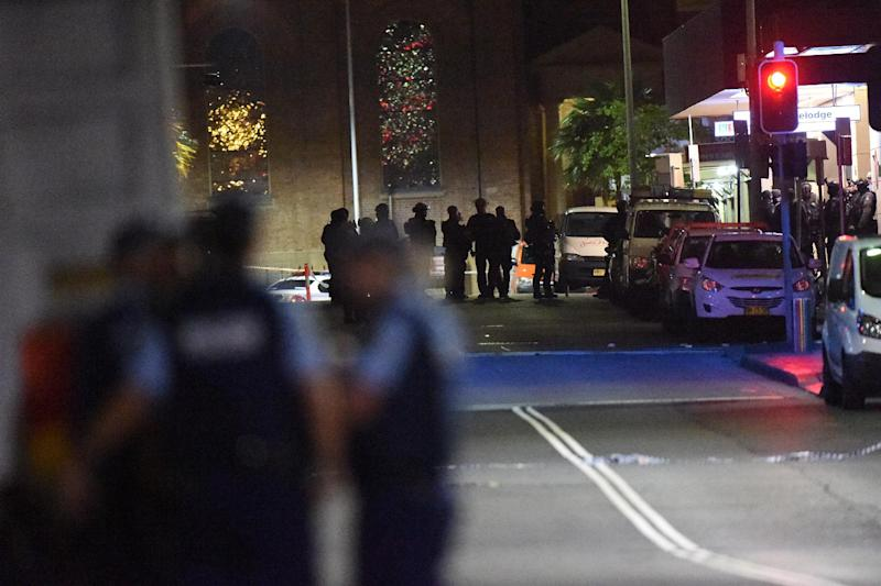 Armed police carry out an operation outside the cafe where a gunman had taken people captive in the central business district of Sydney on December 15, 2014 (AFP Photo/Saeed Khan)